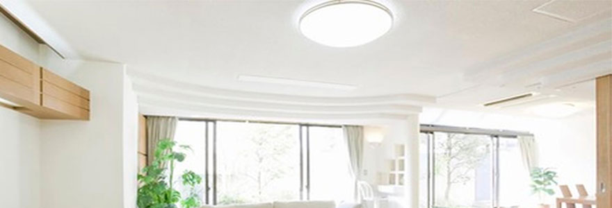 plafonnier LED de forme ronde éclairant un salon moderne et cosy aux teintes grises